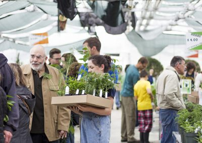 Woman holding plants for man in plant sale checkout line.