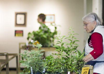 Volunteer pushing cart of plants.