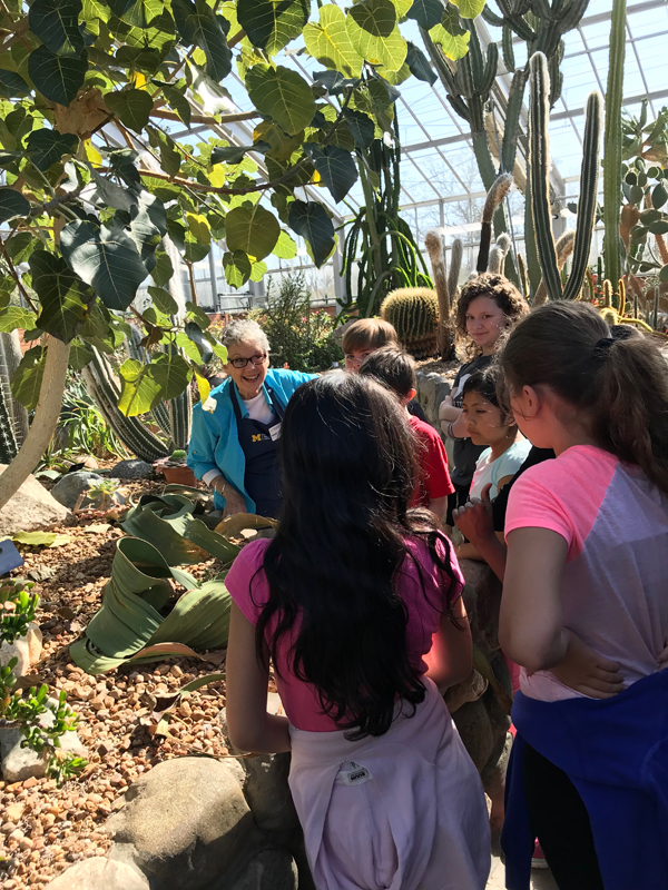 A school field trip with students and docents in teh conservatory at Matthaei